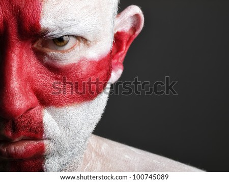 Man with his face painted with the flag of England.  The man is serious and photographic composition leaves only half of the face. - stock photo