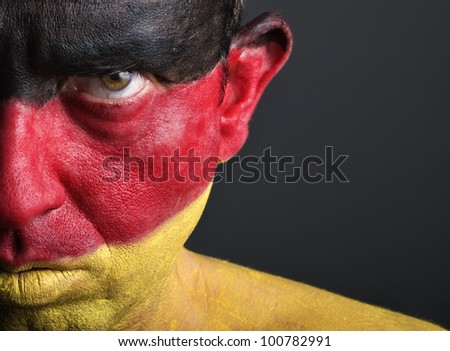 Man with his face painted with the flag of Germany.  The man is serious and photographic composition leaves only half of the face. - stock photo