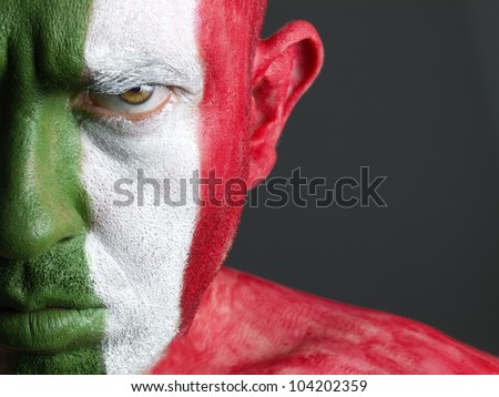 Man with his face painted with the flag of Italy. The man is serious and photographic composition leaves only half of the face. - stock photo