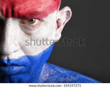 Man with his face painted with the flag of Netherlands.  The man is serious and photographic composition leaves only half of the face. - stock photo