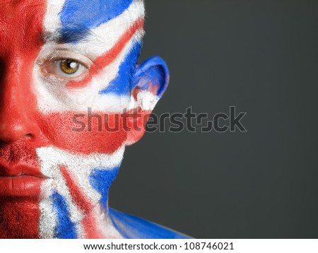 Man with his face painted with the flag of United Kingdom. The man is sad and photographic composition leaves only half of the face. - stock photo