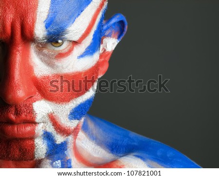 Man with his face painted with the flag of United Kingdom. The man is serious and photographic composition leaves only half of the face. - stock photo