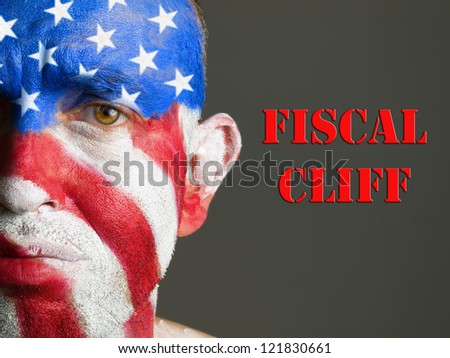 Man with his face painted with the flag of USA and the expression fiscal cliff - stock photo