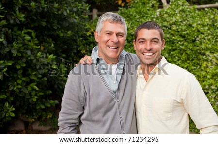 Man with his father looking at the camera - stock photo