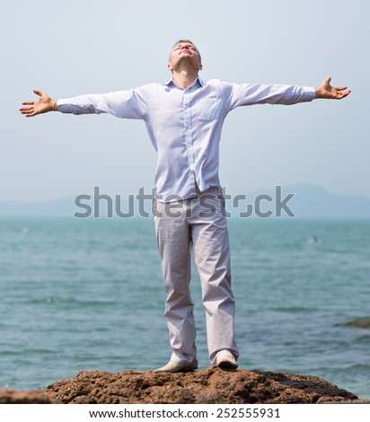 man with his hands against blue sky and sea - stock photo