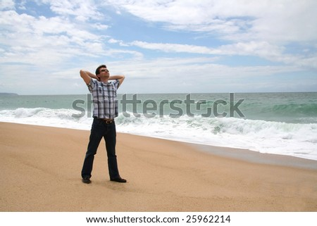 Man with his hands behind the head on the shore of the ocean