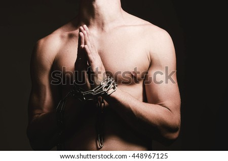 man with his hands chained with strong steel chains