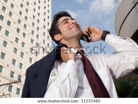 Man with his jacket over his shoulder smiling while talking on the phone - stock photo