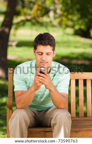 Man with his phone on the bench - stock photo