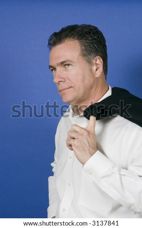man with his suit jacket flung over his shoulder now that the work day is over. - stock photo