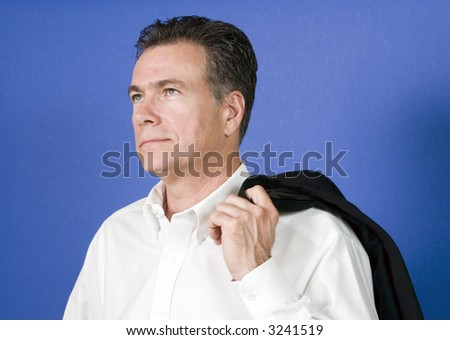 Man with his suit jacket flung over his shoulder with a look of longing on this face. - stock photo