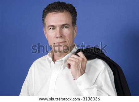 Man with his suite jacket flung over his shoulder with an unsmiling serious expression. - stock photo