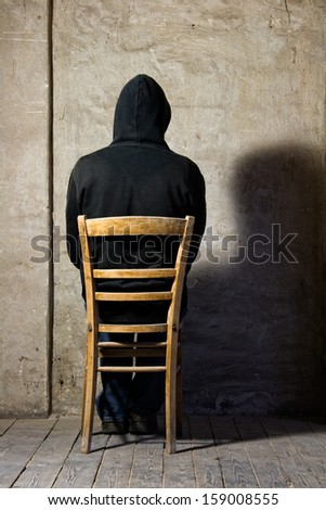 man with hooded jacket sitting in front of an old wall - stock photo