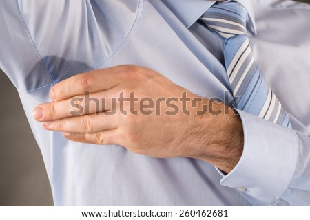 Man With Hyperhidrosis Sweating Touching His Armpit - stock photo
