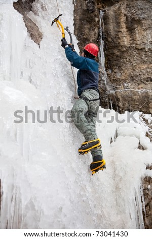 Man with ice axes and crampons climbing on icefall - stock photo