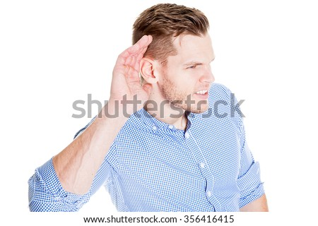 Man with impaired hearing struggling to hear frowning as he holds his hand to his ear in an attempt to improve acoustics