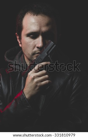 Man with intent to commit suicide, gun and leather jacket, red backlight