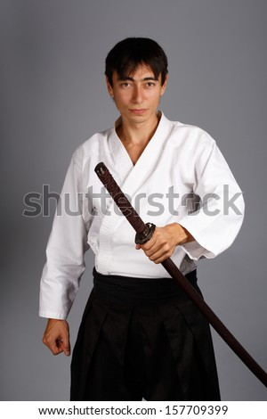 Man with katana sword in scabbard on grey background standing in fighting pose. - stock photo