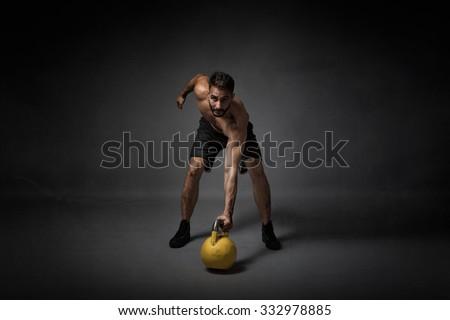 man with kettleball on hand, dark background - stock photo
