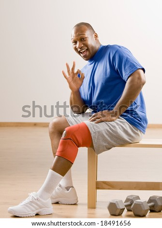 Man with knee brace gesturing the ok symbol in health club