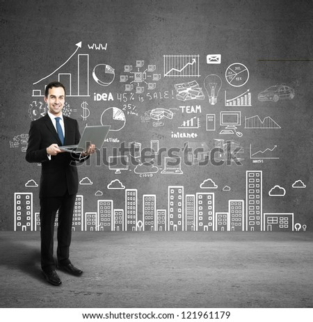 man with laptop and business plan on wall - stock photo