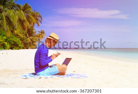 man with laptop and mobile phone on tropical beach