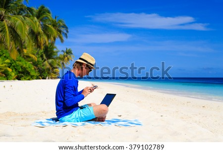 man with laptop and mobile phone on tropical beach - stock photo