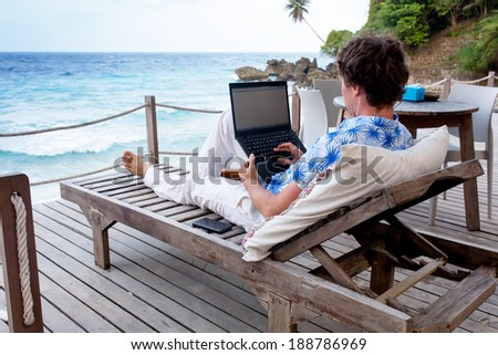 man with laptop and mobile phone running remotely on colorful beach of island, among the palms cafe. - stock photo