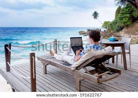 man with laptop and mobile phone running remotely on colorful beach of island, among the palms cafe.