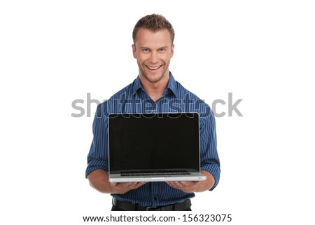 Man with laptop. Cheerful young man holding laptop and smiling while standing isolated on white