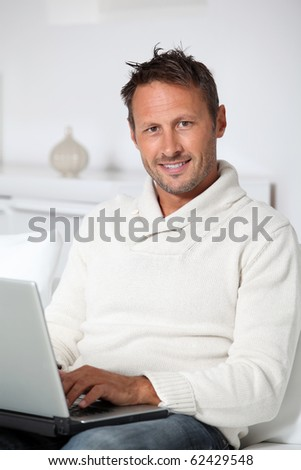 Man with laptop computer sitting in sofa - stock photo
