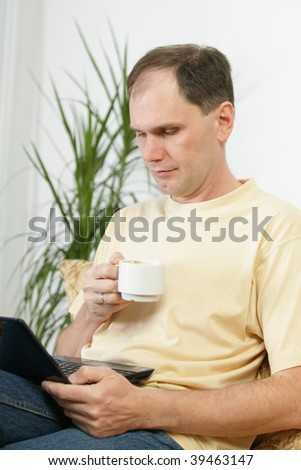 Man with laptop drinking coffee on a sofa