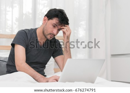 Man with laptop having headache from working at his home office.