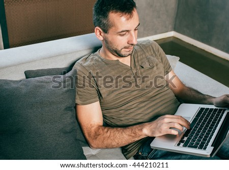 Man with laptop home working  - stock photo