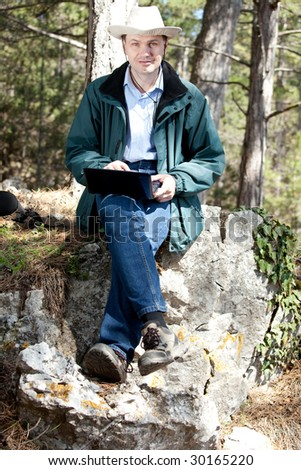 Man with laptop in forest