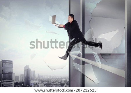 Man with laptop jump through office building window. Fast internet connection concept - stock photo