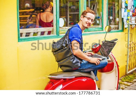 Man with laptop on motorbike - stock photo