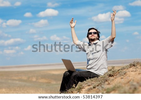 man with laptop on the mountain - stock photo