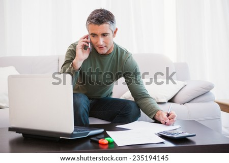 Man with laptop phoning and taking notes at home in the living room - stock photo