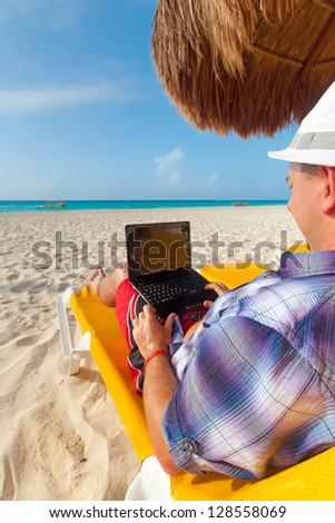 Man with laptop relaxing on the deckchair at the Caribbean sea - stock photo