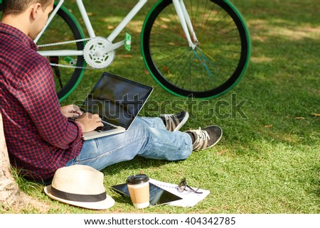 Man with laptop sitting on grass in city park