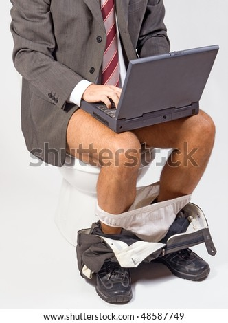 man with laptop sitting on the toilet - stock photo