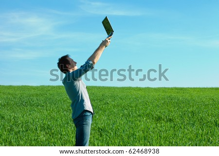 man with laptop standing in a field - stock photo