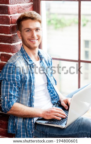 Man with laptop. Top view of handsome young man working on laptop while sitting on the window sill - stock photo