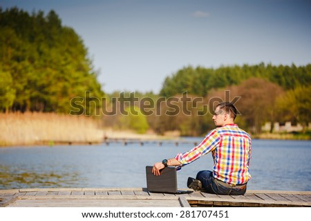 Man with laptop working outdoor near the beautiful lake - stock photo