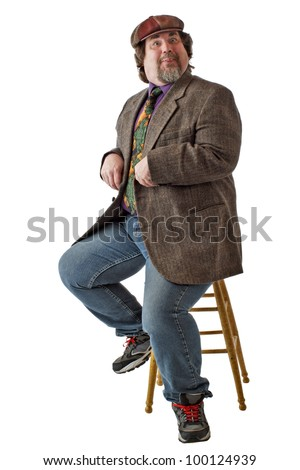 Man with large build sits on stool, dressed casually in tweed cap, jacket and jeans. He is in a funny pose imitating a bird. Vertical, isolated on white background, copy space. - stock photo