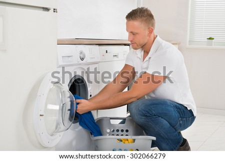 Man With Laundry Basket Loading Washing Machine With Clothes In Kitchen Room