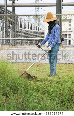 man with lawn mower in network at high voltage substation - stock photo
