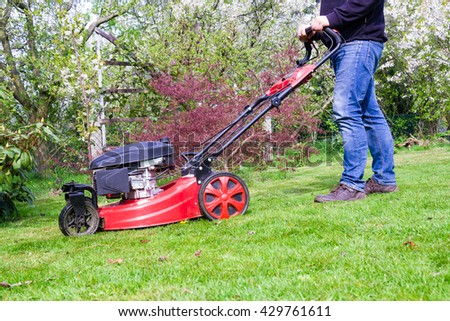 man with lawnmover in garden