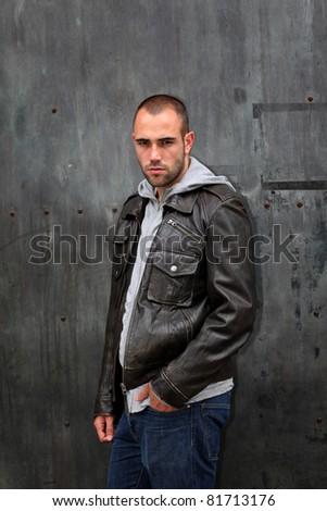 Man with leather jacket standing on metal door - stock photo
